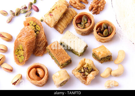 Top view of a variety of Arabic desserts, and ingredients around. On a white background. - Stock Photo