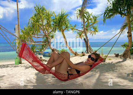 Girl relaxing on a hammock at Bounty beach, Malapascua island, Cebu, Philippines - Stock Photo