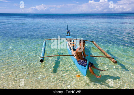 Filipino boy sitting on a small outrigger boat at Bounty beach, Malapascua island, Cebu, Philippines - Stock Photo