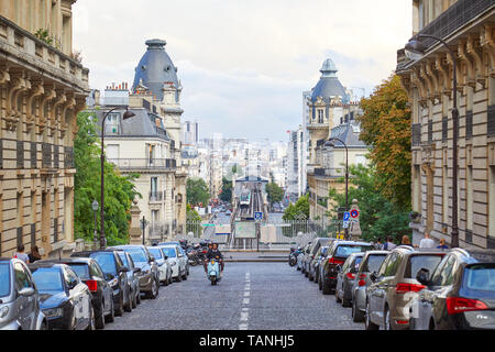 PARIS, FRANCE - JULY 22, 2017: Street in Paris with perspective, people walking and riding moped in France - Stock Photo