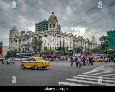 Kolkata, West Bengal / India - April 7, 2019: Cityscape, traffic of a notable city road near Esplanade with a yellow taxi at Chowringhee area, Kolkata - Stock Photo