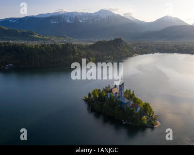 Sunrise aerial view of St Marys church on island of Lake Bled, Slovenia. In background there is castle Bled on rocks and distant mountains in early su - Stock Photo