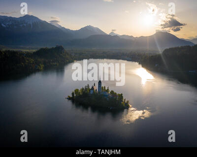Lake Bled church aerial view short time after sunrise. Tower of St. Marys Church of the Assumption church in shadow. There are Julian Alps in backgrou - Stock Photo