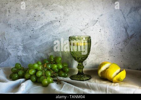 Still life with grapes, lemon and water on the gray background - Stock Photo