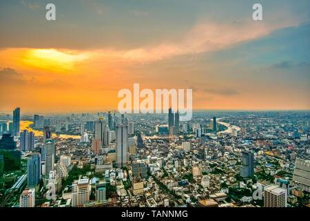 Aerial panoramic view of beautiful orange sunset sky at skyline over Bangkok city central business downtown with curved view of Chao Phraya River.