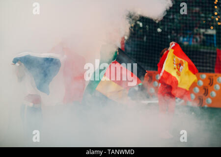Flags Germany, Spain, France during a sports soccer match at a stadium in smoke