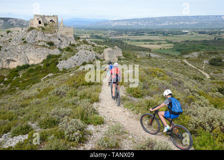 Three Young Boys Mountain Biking & the Château de Roquemartine Les Alpilles Provence France - Stock Photo