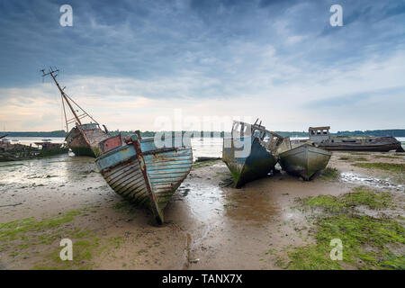 Abandoned fishing boats under a brooding sky at Pin Mill on the River Orwell near Ipswich on the Suffolk coast - Stock Photo