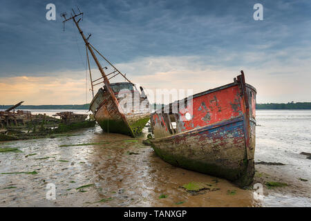 Old boat wrecks under a stormy sky on the River Orwell at Pin Mill on the Suffolk coast - Stock Photo