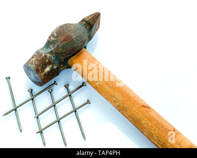 An old hammer with a wooden handle and a bunch of nails. Objects on a light background - Stock Photo