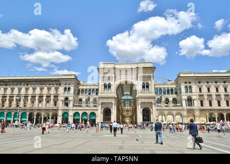 Milan, Italy - July 15, 2016: Busy people and tourists are walking at the Duomo square in the Milan downtown with a view to Vittorio Emanuele Gallery. - Stock Photo