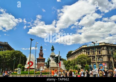 Milan/Italy - July 15, 2016: Panoramic view to the Sforza Castle and the Giuseppe Garibaldi monument in Cairoli square with a crowd of tourists. - Stock Photo