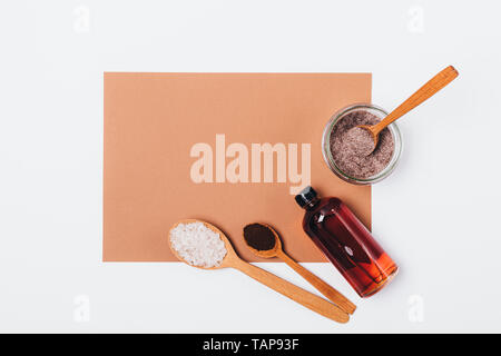 Homemade anti-cellulite coffee scrub with sea salt near jar of fresh made product and bottle of oil on white background, flat lay mockup. - Stock Photo