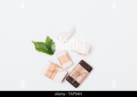 Set of natural handmade soaps of various types next to green leaves on white background, flat lay. - Stock Photo
