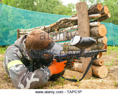 A paintball player who is ready to shoot from hiding. Lying on the ground and shooting.  Immediately before shooting with a gun. Paintball player in p - Stock Photo