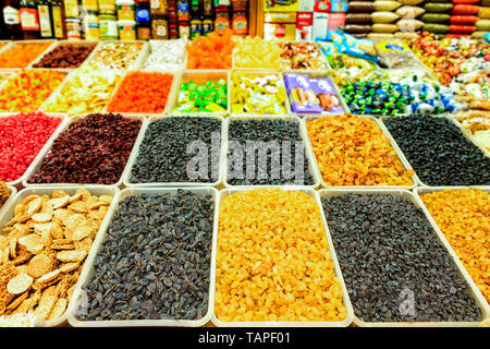 Ingredients for healthy vegetarian food are yellow golden and black raisins sold in trays on the market, compared to other sweets in the blur. - Stock Photo