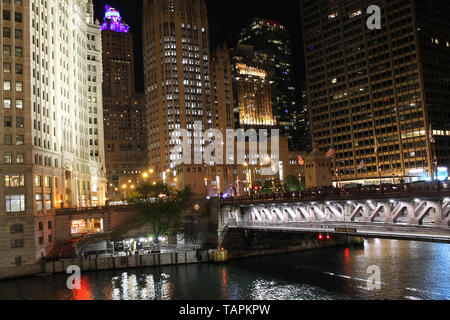 The Wrigley Building, Tribune Tower, 401 N Michigan Ave and the Michigan Ave Bridge along the Chicago River in downtown Chicago, Illinois at night - Stock Photo