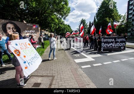 Dortmund, Nordrhein Westfalen, Germany. 25th May, 2019. A demonstrator against racism to the left of the approaching neonazi parade in Dortmund, Germany. Prior to the European Elections, the neonazi party Die Rechte (The Right) organized a rally in the German city of Dortmund to promote their candidate, the incarcerated Holocaust denier Ursula Haverbeck. The demonstration and march were organized by prominent local political figure and neonazi activist Michael Brueck (Michael Brück) who enlisted the help of not only German neonazis, but also assistance from Russian, Bulgarian, Hungarian, an - Stock Photo