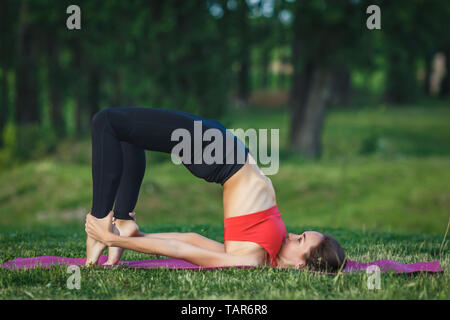 Young woman doing yoga exercises in the summer city park. Health lifestyle concept. - Stock Photo