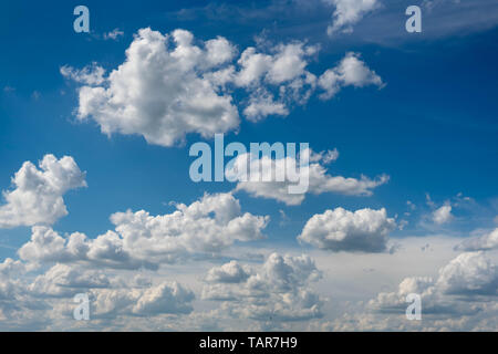 Beautiful blue sky with white clouds and a thin horizon line. Rays The sun breaks through the clouds. - Stock Photo