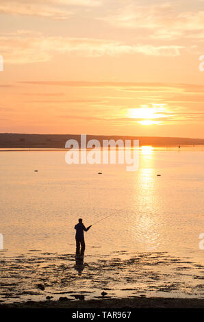 A man saltwater flyfishing in the Fleet lagoon at sunset viewed from the bridge at Ferry Bridge. Ferry Bridge is at the start of the causeway that lea - Stock Photo