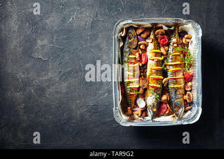 three whole grilled mackerel with lemon, tomatoes, mushrooms, spices and herbs. scomber baked in Aluminum Baking Pan with mushrooms and tomatoes, view - Stock Photo