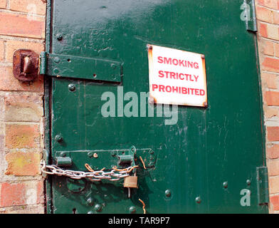 Heavy door chained and padlocked for security - Stock Photo