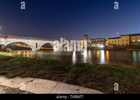 Ponte Pietra at night (Stone bridge). I century B.C. - the oldest Roman monument in Verona, UNESCO heritage site, and the river Adige, Veneto, Italy - Stock Photo