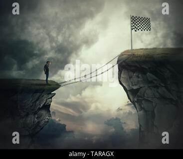 Success dilemma as a young man stand on a edge of a cliff needs to go the other side to reach the finish flag crossing a broken bridge. Overcome probl - Stock Photo