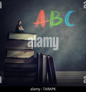 Curious student guy seated on the top of a huge atack of books looking at the blackboard with ABC letters written. Education and knowledge concept. Te - Stock Photo