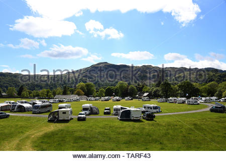 Dozens of caravans and campers parked up at Grasmere village in Cumbria in the Lake District for a camping holiday in the good sunny weather - Stock Photo