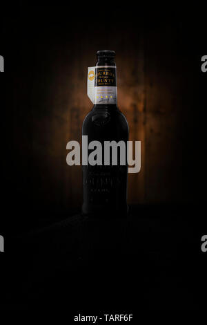 Goose Island Bourbon County stout craft beer against a wooden background. - Stock Photo