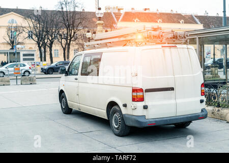 White repair and service van with ladder and orange light bar on roof at city street. Assistance or installation team vehicle. - Stock Photo