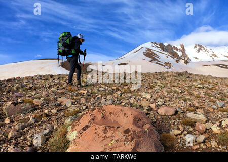 Woman tourist with a backpack on her back goes hiking on a rocky slope to a snowy mountain - Stock Photo