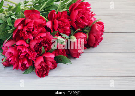 Bouquet of dark pink peonies lying on gray wooden table - Stock Photo