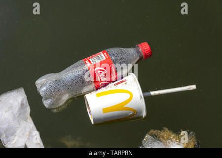Empty Coca-Cola bottle and McDonalds paper cup floating in Walsall Canal, Walsall, West Midlands, England, United Kingdom - Stock Photo
