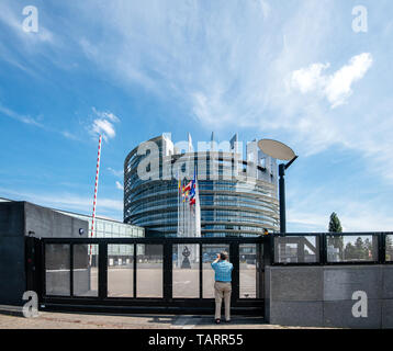 Strasbourg, France - May 26, 2019: Seniopr man taking photograph through the closed gate of the European Parliament headquarter with all European Union flags waving - clear blue sky in background