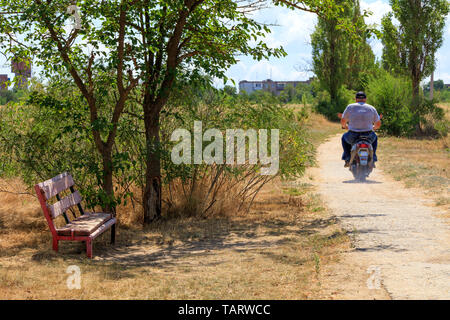 A bench in the shade of a tree, old and weathered, against the backdrop of a rural landscape and a resident who is riding a scooter along an old concr - Stock Photo