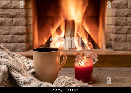 Big mug with hot tea, and a candle , wool scarf, near cozy fireplace, in country house, hygge, home sweet home. - Stock Photo