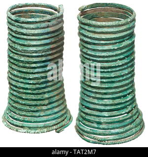 A pair of Late Bronze Age spiral bracelets, 13th century BC, Of triangular section, the flat side facing to the inside and the pointed side to the outside, wound to a spiral. The edge is rounded at top and the exterior is incised, the lower edge twisted and hammered to a square profile. The top and bottom terminals hammered flat and bent backward. Height of either piece ca. 14.5 cm. Width 6.5 cm - 9 cm. Green patina with sporadic oxide colourings and encrustations, minimal chippings at the edges. Provenance: South German private collection, purch, Additional-Rights-Clearance-Info-Not-Available - Stock Photo