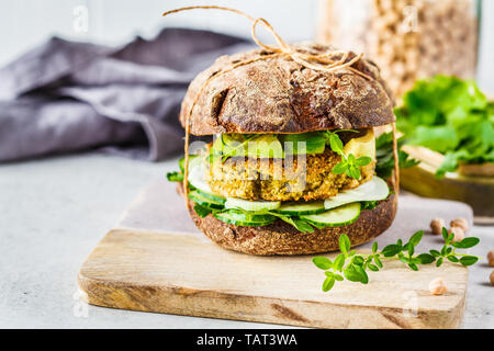 Vegan sandwich with chickpea cutlet, avocado, cucumber and greens in rye bread. - Stock Photo