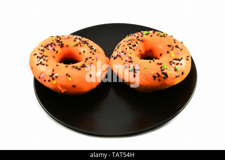 Orange donuts with sprinkles on black plate on white background - Stock Photo