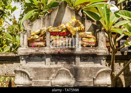 Triple stone altar dedicated to Trimurti - Brahma, Shiva and Vishnu with traditional Hindu Balinese offerings canang sari. Bali, Indonesia. - Stock Photo