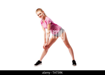 Sport exercises on a white background, fitness concept. A young woman in comfortable sportswear (shorts and top) is smiling charmingly and doing wide  - Stock Photo
