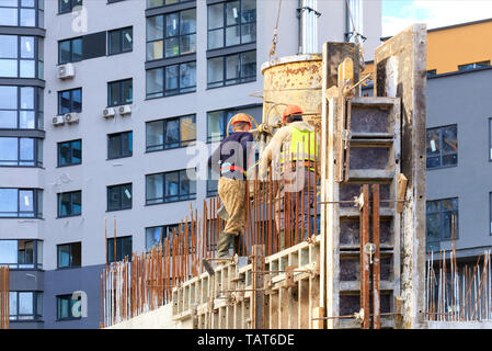 Workers poured concrete in the formwork of the walls on the construction of the house against the background of a modern residential building. - Stock Photo