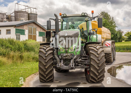 Big hefty tractor with farm in the background - Stock Photo