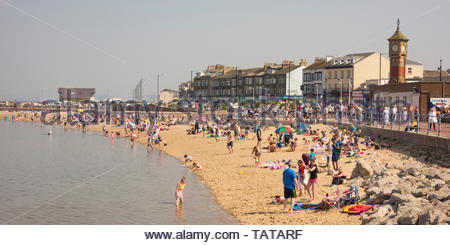 Visitors on the beach on a sunny Easter Bank Holiday at Morecambe, Lancashire, England, UK - Stock Photo