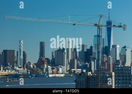 DOWNTOWN MANHATTAN SKYLINE HUDSON RIVER WITH CONSTRUCTION CRANES HOBOKEN NEW JERSEY USA - Stock Photo