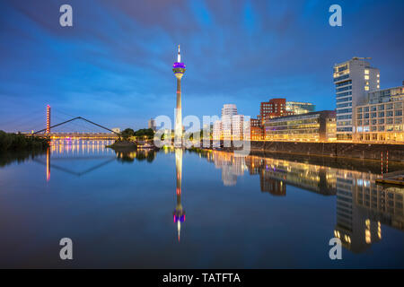 Dusseldorf, Germany. Cityscape image of Düsseldorf, Germany with the Media Harbour and reflection of the city in the Rhine river, during twilight blue - Stock Photo