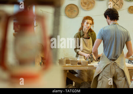 Pleasant colleagues. Curious ginger curly girl listening to her master while staying in decorated workshop and processing clay - Stock Photo